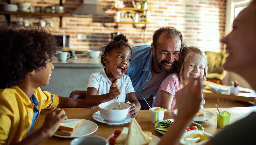 Playful family enjoying breakfast with each other
